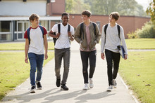 Group Of Male Teenage Students Walking Around College Campus