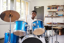 Male Teenage Pupil Playing Drums In Music Lesson