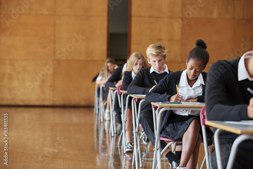 Fotografia  Teenage Students In Uniform Sitting Examination In School Hall
