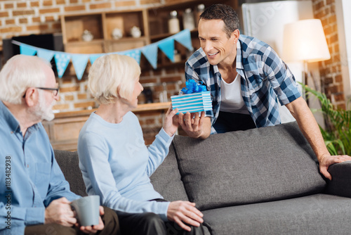 Charming Young Man Giving A Birthday Present To His Elderly Mother Sitting On The Sofa Next Her Husband