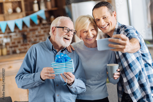 Cheerful Young Man Taking Selfies With His Elderly Parents During The Celebration