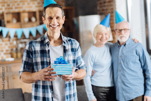 Happy Birthday Man Pleasant Elderly Posing With His Present While Parents Hugging In The Background And All Of Them Wearing Blue