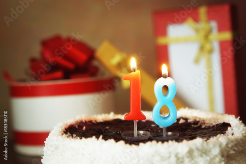 Photo Eighteen years birthday. Cake with burning candle and gifts