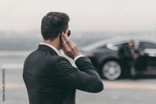 Fotografía  handsome bodyguard standing and listening message with security earpiece on heli