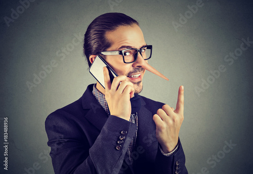 Fotografija  Sly liar business man with long nose talking on mobile phone isolated on gray wall background
