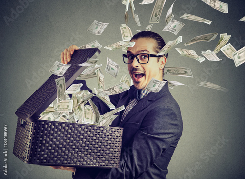 Fototapeta Excited successful man opening a box with money flying out away  obraz