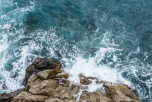 Aerial View Of Ocean Wave Crashing On Rocky Cliff With White Spray And Foam On Deep Blue Sea Water After Storm