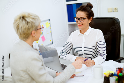 Fototapety, obrazy: Smiling attractive middle aged successful financial assistant woman with eyeglasses sitting in front of the woman customer and taking a bank card in the office.