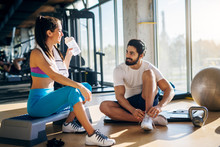Attractive Young Fitness Couple Resting On A Black Mat And Stepper With Kettler Ball And Gloves Near Them In The Gym.