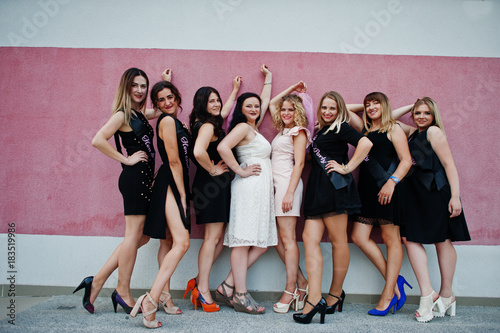 Fototapeta Group of 8 girls wear on black and 2 brides at hen party posed against pink wall. obraz na płótnie