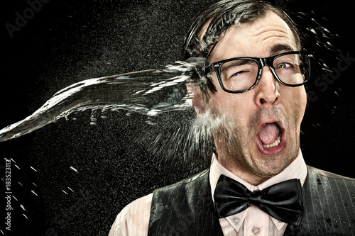 Fototapeta surprised elegant nerd with glasses hit by cold water spray on black background
