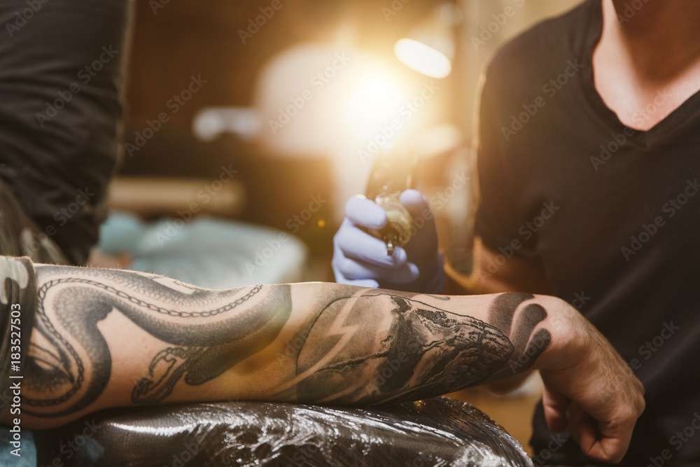 Fototapeta Close up of professional tattooer artist doing picture on hand of man by machine black ink from a jar. Tattoo art on body. Equipment for making tattoo art. Master makes tattooed in light studio.