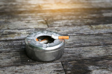Cigarette With Ashtray On Wood Table