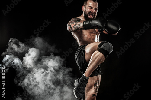 Sportsman muay thai boxer fighting on black background with smoke Canvas Print