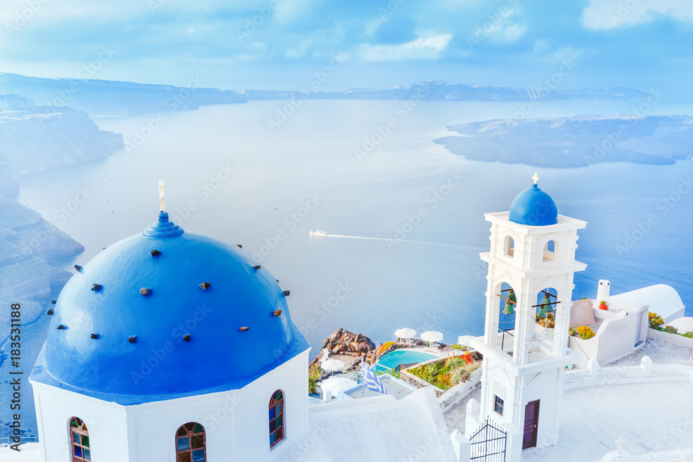 Fototapeta Greece, Santorini island in Aegean sea. Breathtaking scenery with blue domed church on foreground and epic island panorama in background.