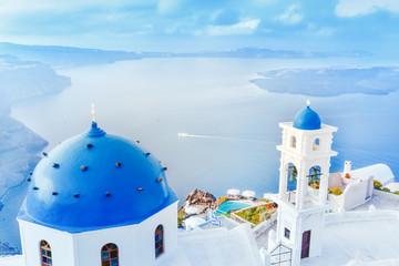 Grecja, wyspa Santorini w Morzu Egejskim. Zapierająca dech w piersiach sceneria z niebieskim domed church na pierwszym planie i epickiej panoramy wyspy w tle.