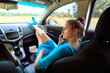 Girl in car sitting on passenger seat with feet on car dashboard and talking on mobile phone. Young woman relaxing with feet on dashboard. Freedom travel concept. Spending weekend in roadtrip