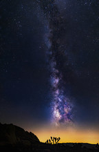 Vertical Orientation Of The Milky Way Galaxy Along The Starry Night Sky In Joshua Tree National Park With A Desert Foreground On Orange Light Pollution.  The Image Depicts Astrophotography And Nature.