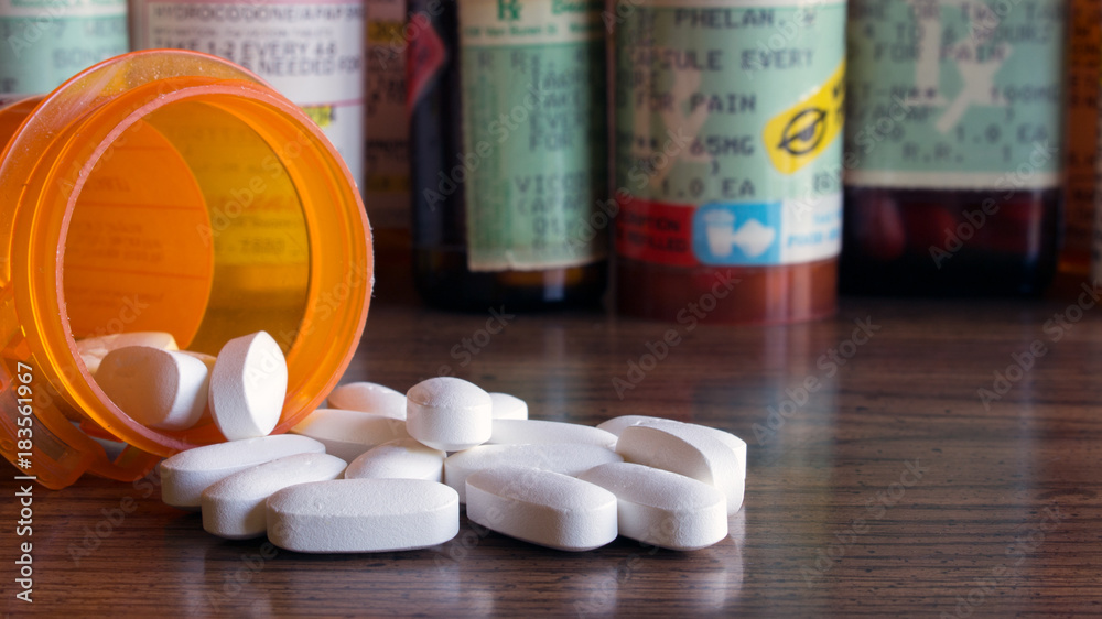 Fototapeta Prescription opioids with many bottles of pills in the background. Concepts of addiction, opioid crisis, overdose and doctor shopping