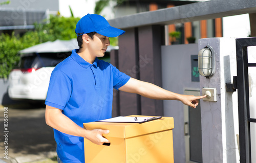 Delivery concept - Happy delivery person in blue uniform holding cardboard box s Canvas-taulu