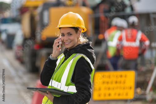 female construction woman using electronics on construction site Slika na platnu