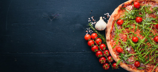 Fototapeta Pizza Primavera. Cherry tomatoes, arugula, cheese. On a wooden background. Top view.