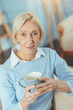 canvas print picture - Good tea. Pleasant aged woman sitting in her living room and holding a big mug while feeling satisfied with the taste of her new tea