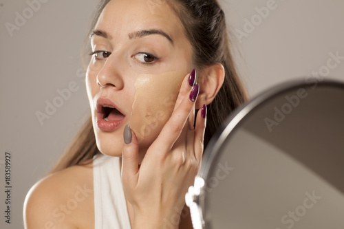 young woman applying a liquid foundation on her face with her fingers Fototapete