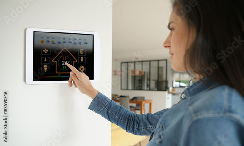 Fotografía  Woman using smart wall home control system