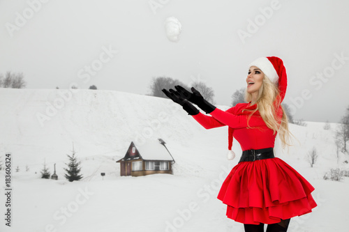 Fotografie, Obraz  Beautiful sexy blonde woman wearing a red dress and a Santa's hat on a background of mountains and snow
