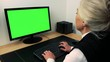 Old caucasian woman works on computer in home - green screen