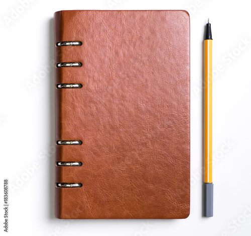 Leather cover notebook with a yellow pen on white background