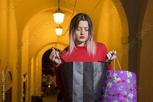 Fotografering  Giovane ragazza che guarda perplessa l'interno della bag