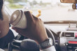 Man eating donuts with coffee while driving car - multitasking unsafe driving concept