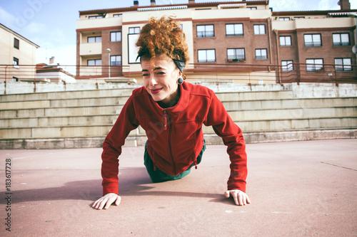 Mujer joven que empieza a hacer ejercicio de flexiones Fotobehang