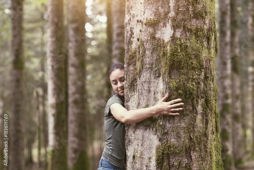 Obraz na plátně  Smiling woman hugging a tree