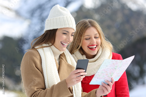 Photo  Two tourists reading a map in winter holidays