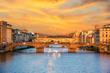 Beautiful City View With The Famous Medieval Stone Bridge Ponte Vecchio Over The Arno River In Florence, Italy At Sunset. Place Of Pilgrimage For Tourists.
