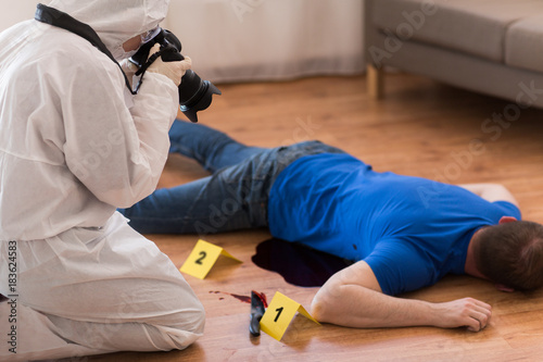 criminalist photographing dead body at crime scene - Buy
