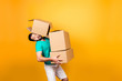 canvas print picture - It's moving day! Busy funny guy in casual clothes is carrying big boxes in his hands and trying to keep one using his head, isolated on yellow background