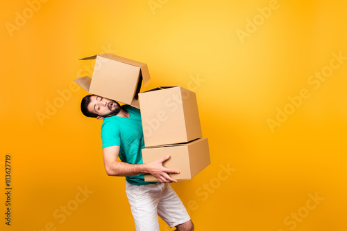 Obraz It's moving day! Busy funny guy in casual clothes is carrying big boxes in his hands and trying to keep one using his head, isolated on yellow background - fototapety do salonu