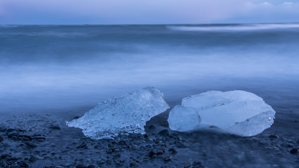 Glacial fragments of ice at Jokulsarlon glacier black beach at sunset, Iceland