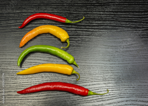 Fotografía  Colorful chili peppers on a wooden table.
