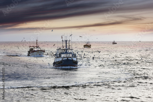 Homecoming: Tired fishermans ships approaching after a hard day