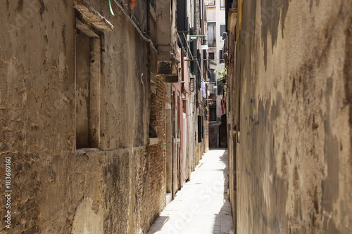 Deurstickers Smal steegje View of a narrow street with old, historical buildings in Venice