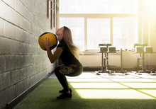 Woman Doing Exercise With Heavy Medicine Ball In Gym