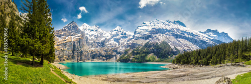 Photo Stands Road in forest Amazing tourquise Oeschinnensee with waterfalls in Swiss Alps
