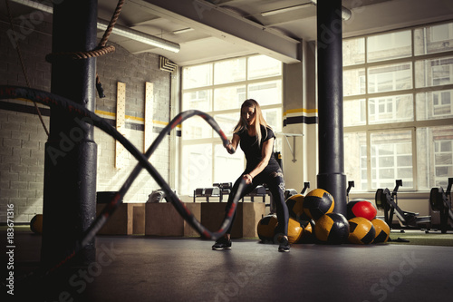 Fotografía  Woman training with battle ropes in gym