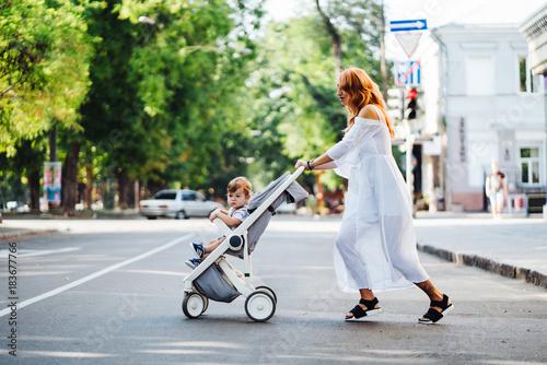 Fotografia, Obraz  mom with a stroller crosses the road