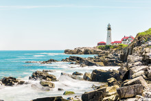 Cliff Rocks Side View Shore With Portland Head Lighthouse In Fort Williams Park In Cape Elizabeth, Maine During Summer Day